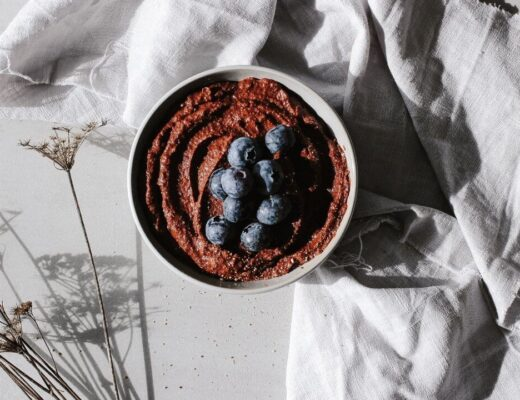 Schüssel mit veganer Schoko Hummus und Blaubeeren
